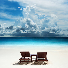 Relaxing on remote beach with raining cloud