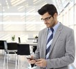 Businessman using cellphone in office lobby