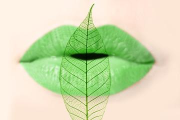 Bouche de femme verte et feuille