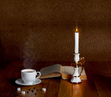 Hot cup of fresh coffee on the wooden table with  candle and boo