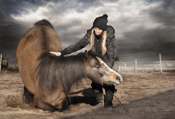 Woman hugging kneeling horse,trick training, cloudy weather
