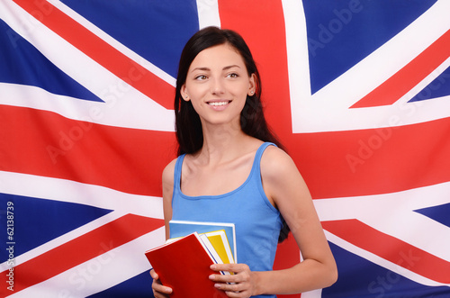 Learn English.Beautiful student holding books looking up.