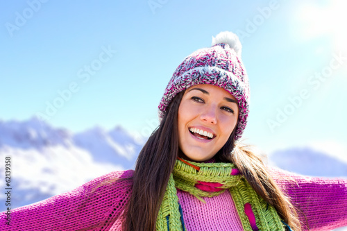 Happy smiling girl in winter mountains.