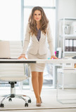 Full length portrait of business woman standing in office