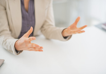 Closeup on business woman explaining something using hands