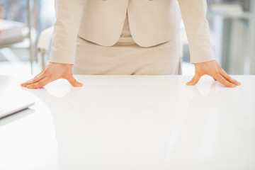 Closeup on business woman leaning on desk