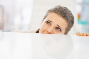 Frightened business woman looking out from desk