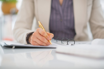 Closeup on business woman writing in document