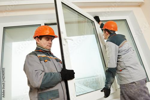 Leinwandbild Motiv two workers installing window