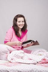 девушка в кровати читает журнал