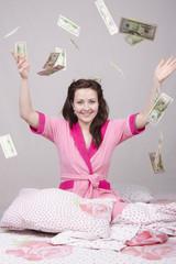 на девушку в постели сыпятся деньги
