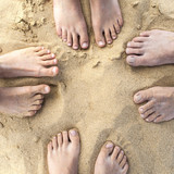 feet of family at the sandy beach