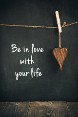 wooden heart on blackboard with text  - loving life concept