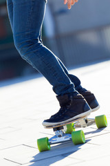 Legs of young boy skating down the street