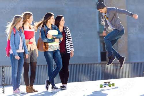 A group of Friends having fun with skate in the street