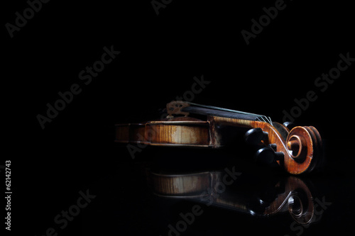 Old scratched violin, reflected in black mirror surface