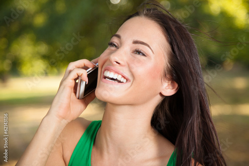 Young woman with a smile on his face using mobile phone