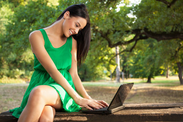 Attractive young woman with toothy smile using laptop outdoors