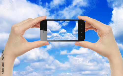 Woman hands hold smart phone with sky close-up.