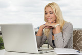 Beautiful young business woman with toothy smile using laptop