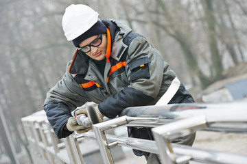 worker polishing metal fence barrier