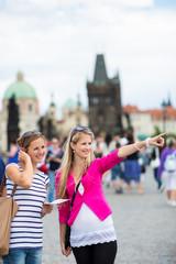 Two female tourists walking along the Charles Bridge