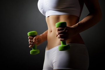 Studio photo of young woman lifting dumbbell