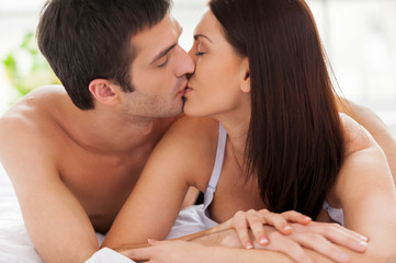 Loving couple kissing in bed.