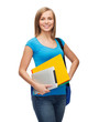 smiling student with bag, folders and tablet pc