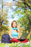 Woman sitting on grass in park and working on laptop