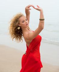 Beautiful nude woman in red fabric posing on sea beach