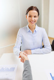 smiling businesswoman shaking hand in office