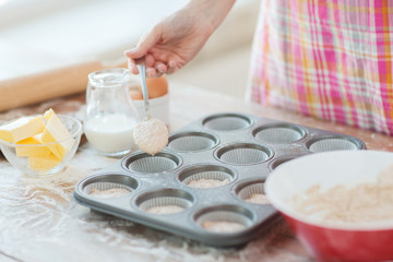 close up of hand filling muffins molds with dough
