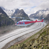Helicopter above the mountains and glacier.