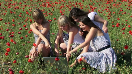 Women using laptop in a field