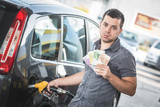 Man with Banknotes at Gas Station