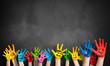 angemalte Kinderhände vor Kreidetafel