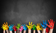 Leinwanddruck Bild - angemalte Kinderhände vor Kreidetafel