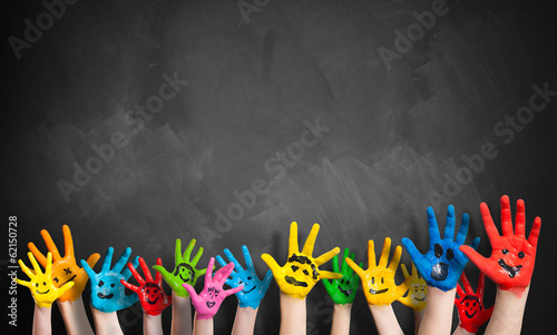 Leinwanddruck Bild angemalte Kinderhände vor Kreidetafel