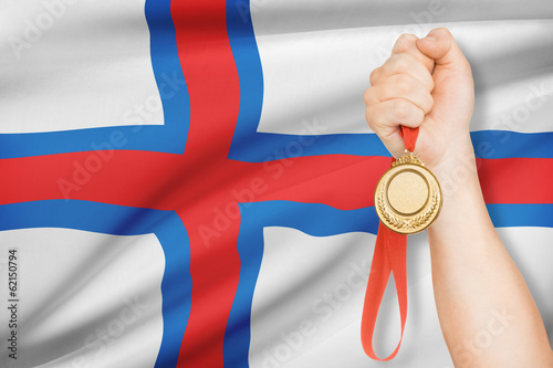 Medal in hand with flag on background - Faroe Islands