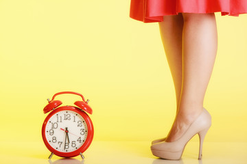 Female legs in high heels and red clock. Time for femininity.