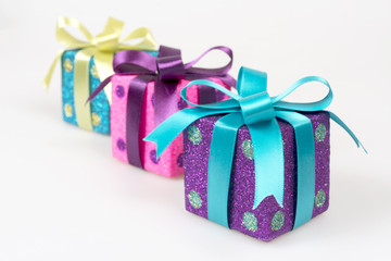 Colorful gift boxes with shiny ribbons over white background.