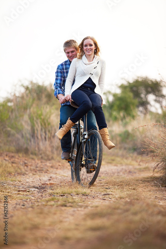 canvas print picture Happy couple riding old bicylce on dirt road