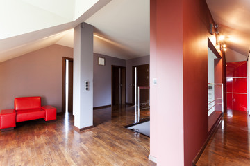 Grey corridor with red armchair