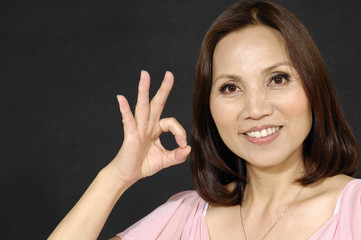 woman doing the ok sign on black