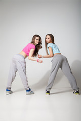 cool looking two dancing women on grey background