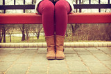Young girl sitting on a bench in red pants and brown boots