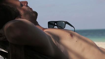 Man sleeping on sunbed by the sea
