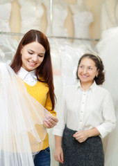 bride chooses bridal veil at shop of wedding fashion