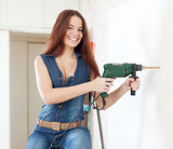 Happy woman in overalls with drill